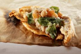 סלט חצילים וגרגרי חומוס על מצע קרעי פיתה קלויה בשמן זית ושום