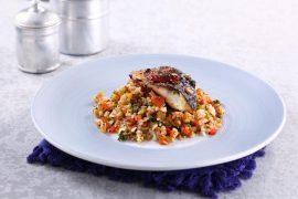 אורז מלא ארוך בסגנון ספרדי, עשיר בירקות מוגש עם דג מוסר אפוי